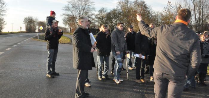 Der örtliche Stadtrat Jürgen Adler weist mit erhobenem Zeigefinger auf die B8 Kreuzung und ihre Gefahren hin.